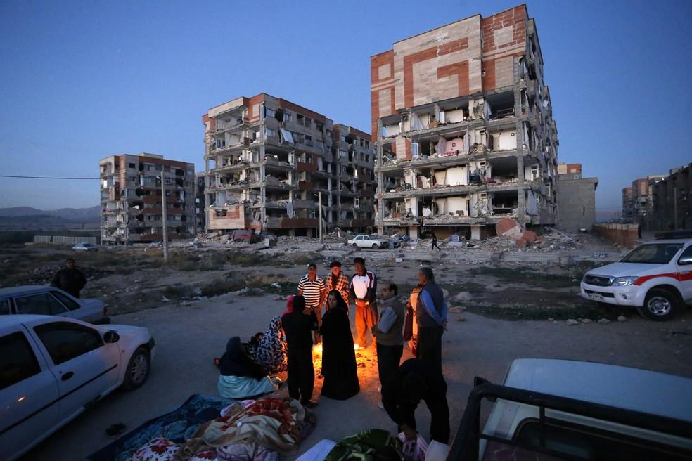 Sobreviventes do terremoto se esquentam em fogueira em frente a prédios destruídos na cidade de Sarpol-e-Zahab, no oeste do Irã, na manhã desta segunda (13) (Foto: Pouria Pakizeh/ISNA via AP)