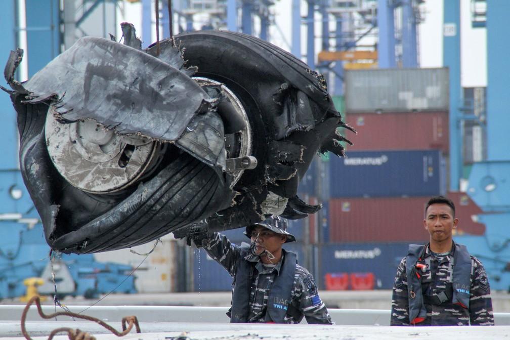 Integrantes de equipe de resgate descarregam um par de pneus do voo da Lion Air JT 610, recuperado no mar, no porto de Jacarta, nesta segunda-feira (5) — Foto: Azwar Ipank / AFP