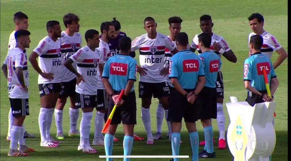 Jogadores do São Paulo recebem dentro do campo a notícia de que jogo com Goiás foi adiado  — Foto: Reprodução TV Globo