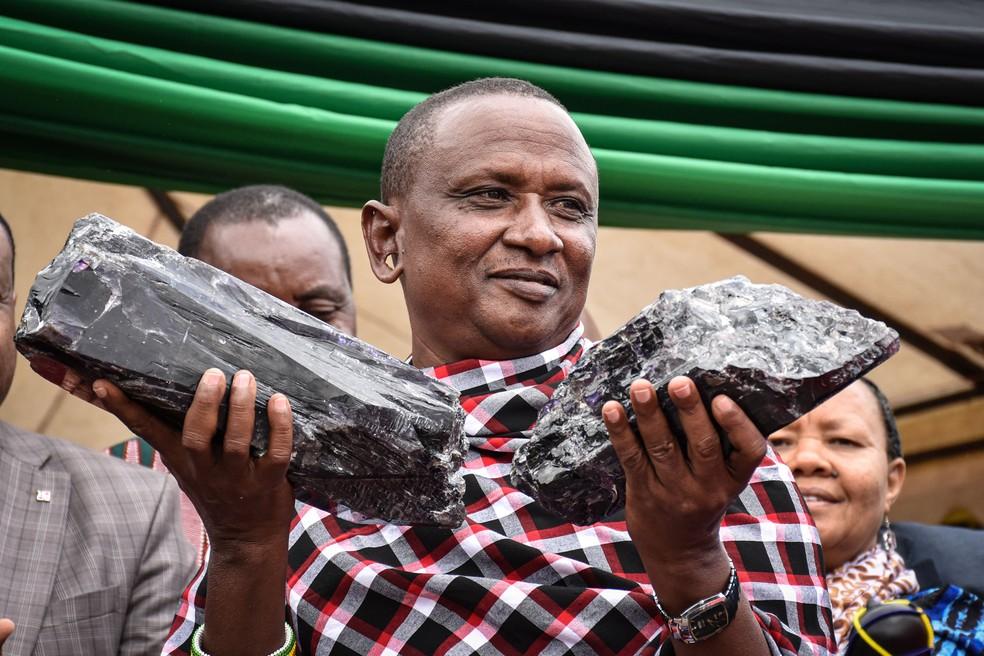 Mineiro Saniniu Kuryan Laizer, de 52 anos, é fotografado com as duas maiores pedras tanzanitas do país, na quarta-feira (25)  — Foto: Filbert Rweyemamu / AFP