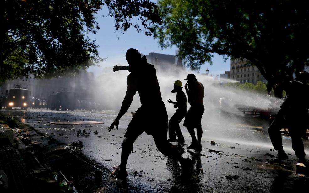 Manifestantes recebem jatos de água disparados pela polícia durante protesto contra a reforma da previdência em Buenos Aires, na Argentina, na segunda-feira (18) (Foto: AP Photo/Victor R. Caivano)