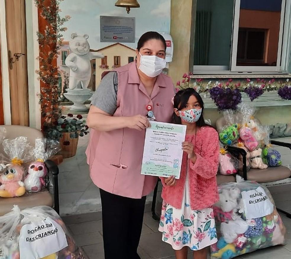 A Psicóloga do GPACI, Evelin de Araujo entregou uma carta de agradecimento à Maria Clara pela doação dos ursinhos — Foto: Arquivo Pessoal