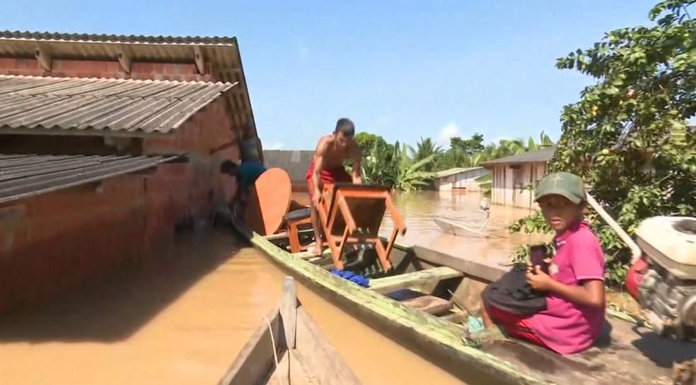 Morador tirar coisas de dentro de casa após ela ter sido invadida  — Foto: Reprodução/ Rede Amazônica Acre