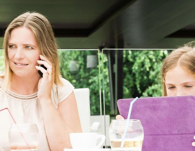 Mãe e filha usando celular  (Foto: Thinkstock)