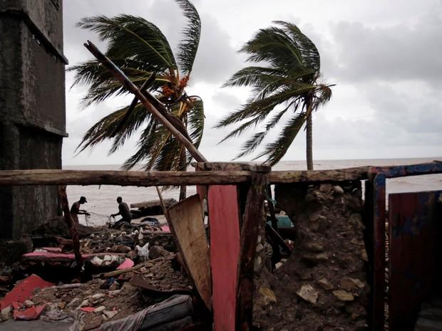 Pescadores consertam redes perto das ruínas de uma casa destruída por passagem do furacão Matthew em Les Cayes, no Haiti, na quarta (5) (Foto: Reuters/Andres Martinez Casar)