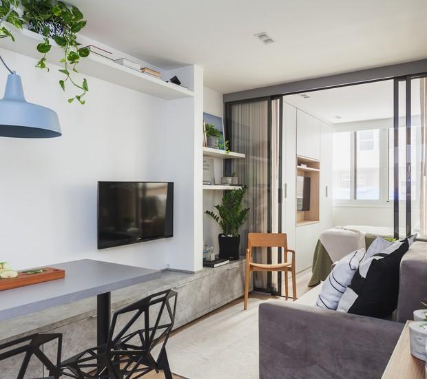 A marcenaria se estende por toda a parede da televisão, servindo como armário, gavetas, banco e aparador (Foto: Divulgação)