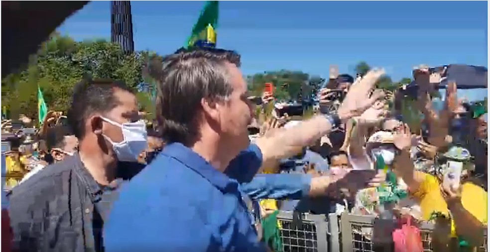 Sem máscara, Bolsonaro percorreu a pé o cercado em frente ao Palácio do Planalto e cumprimentou seus apoiadores — Foto: Reprodução