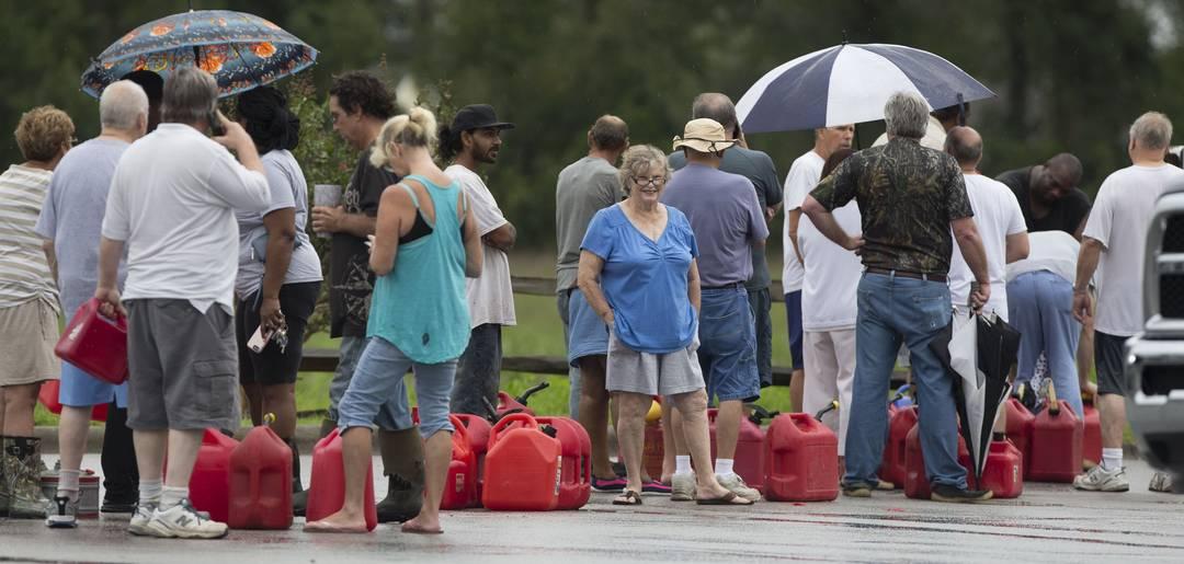 Mais pessoas esperam na fila para encher galões com gasolina em um posto em River Bend, no estado da Carolina do Norte, Estados Unidos