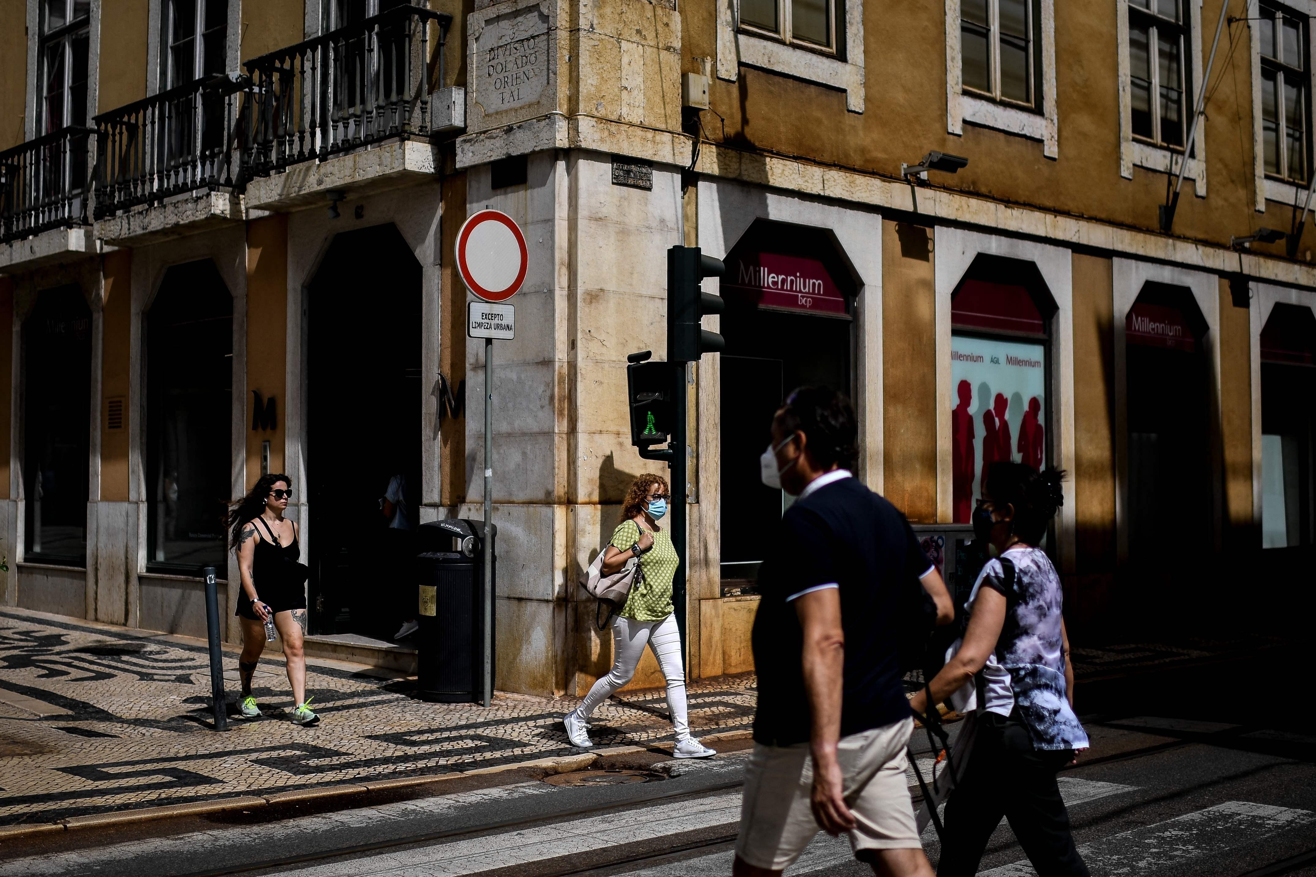 Pessoas com máscara e sem caminham pela baixa de Lisboa