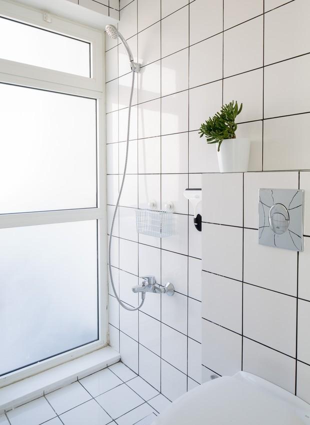 As áreas de cozinha e do banheiro são revestidas em azulejos brancos combinando com o rejunte preto  (Foto: Reprodução/Dezeen)