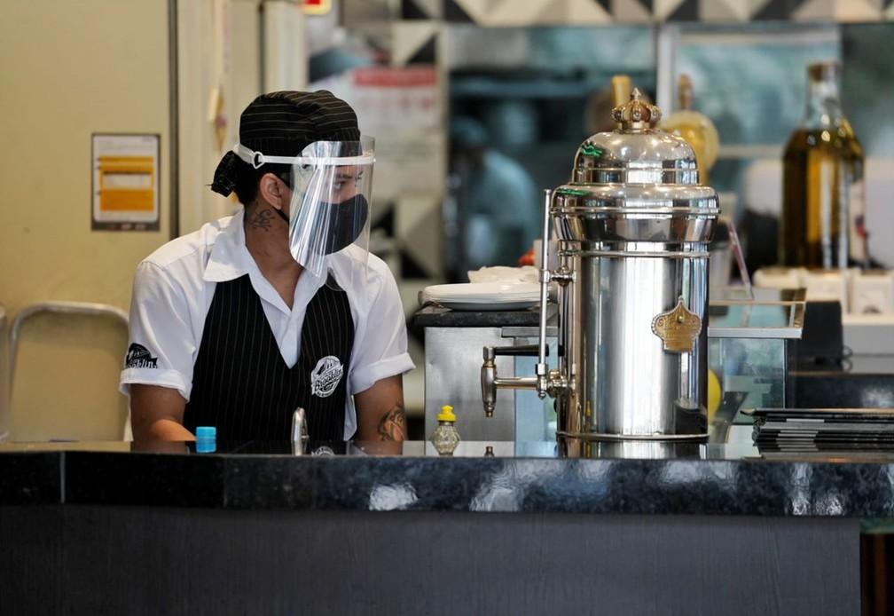 Funcionária de restaurante em SP usa máscara e protetor facial na reabertura para o público — Foto: Marcelo Brandt/G1