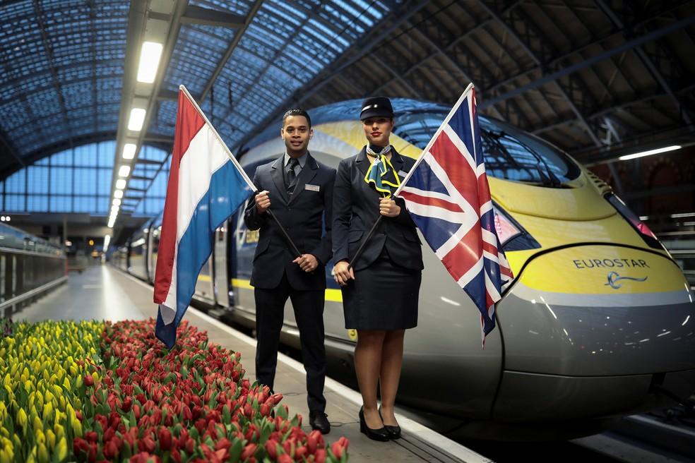 Funcionários da Eurostar seguram as bandeiras do Reino Unido e da Holanda em frente ao trem que liga Londres a Amsterdã  (Foto: Simon Dawson/Reuters)