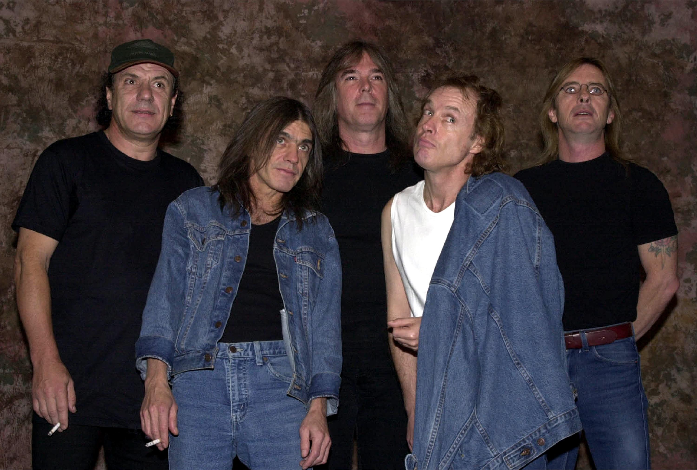 Malcolm Young (1953-2017), de casaco jeans e com um cigarro na mão, ao lado de seus colegas de AC/DC, em foto do ano 2000 (Foto: Getty Images)