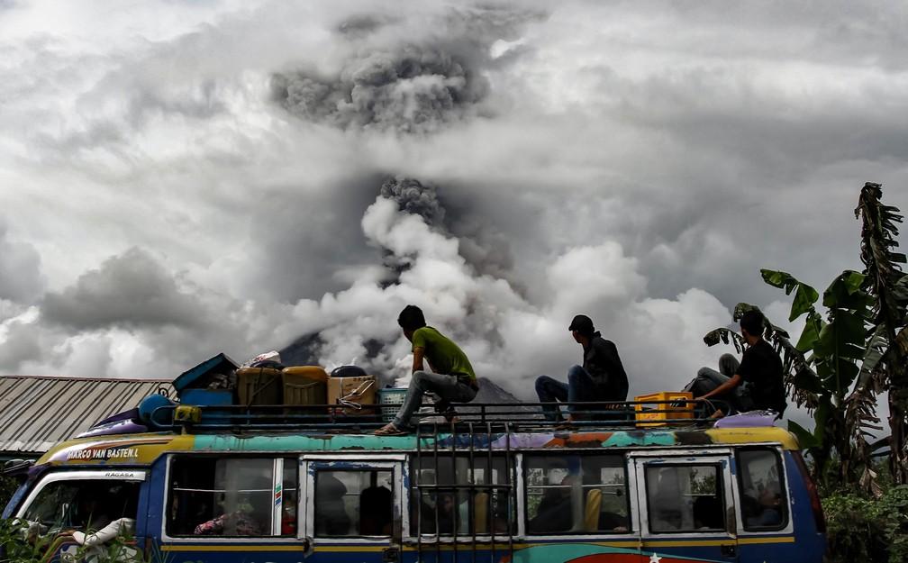 2 de janeiro - Passageiros em um ônibus observam enquanto o mounte Sinabung solta densas nuvens de fumaça em Karo, na Indonésia (Foto: Ivan Damanik/AFP)