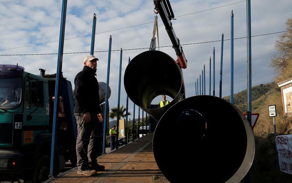 Membros da equipe de resgate transportam tubos, que serão usados na construção de túnel paralelo para tentar chegar até o menino Julen, que caiu em um poço em Totalán, na Espanha, em foto de quinta-feira (17) — Foto: Reuters/Jon Nazca
