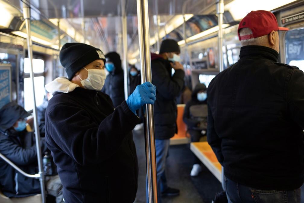 Vários passageiros usam máscaras na tentativa de evitar a contaminação pelo novo coronavírus no metrô, no distrito do Brooklyn, em Nova York, na quarta-feira (25) — Foto: David Boe/AP