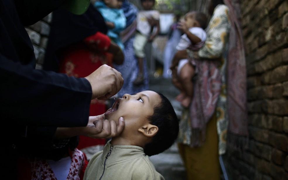 Menino recebe vacina contra pólio enquanto outras crianças aguardam por suas vezes em um beco de um bairro cirstão de Islamabad, no Paquistão. (Foto: Muhammed Muheisen/AP)