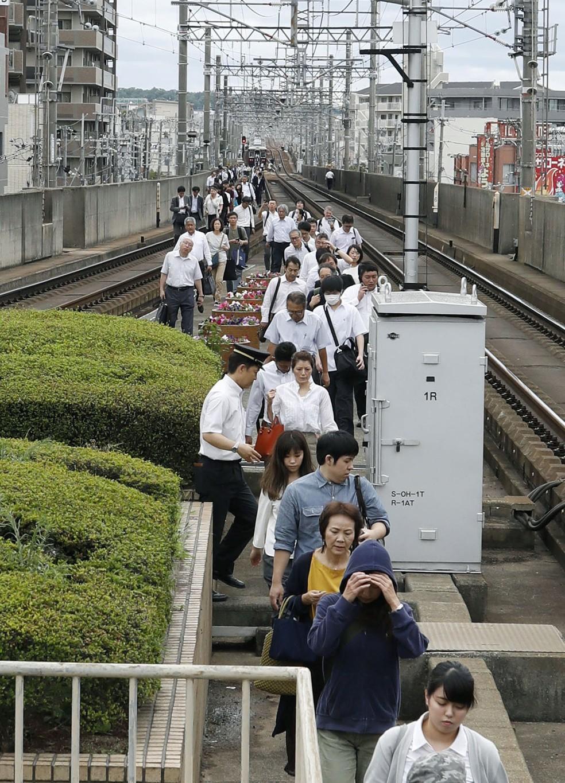 Passageiros andam pelos trilhos após trem parar em Osaka (Foto: Kyodo/via Reuters)