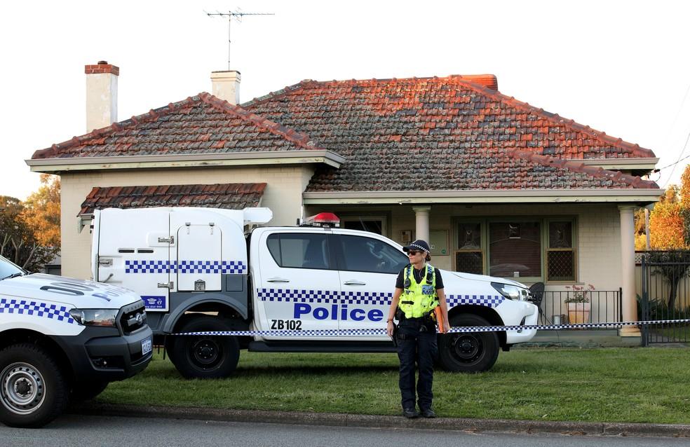 -  Policial em frente a residência em Perth, na Austrália, em que 5 pessoas foram encontradas mortas  Foto: Richard Wainwright/AAP via Reuters