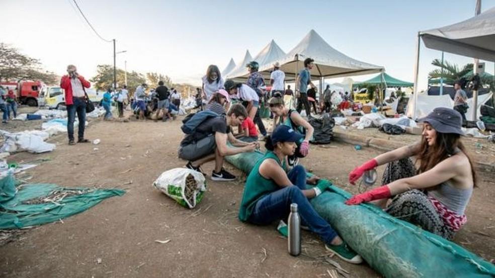 Voluntários armam cilindros flutuantes para conter o derramamento — Foto: Getty Images/BBC