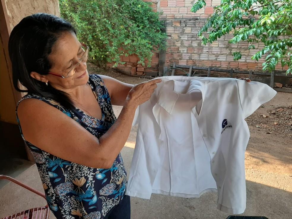 Maria Natália Marinho observa o uniforme de fiscal de loja que usou nos anos em que trabalhou no Supermercado Gonçalves — Foto: Diêgo Holanda/G1
