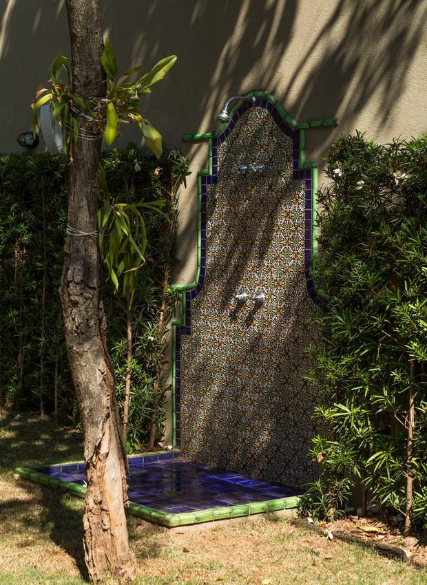 O tronco do outro jasmim-manga que fica nos fundos do jardim serve de apoio para as orquídeas. Logo atrás fica um chuveirão feito de ladrilho hidráulico (Foto: Edu Castello / Editora Globo)
