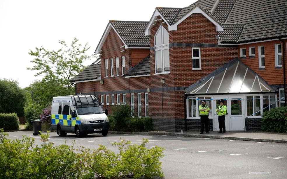 Policiais monitoram entrada da igreja do Centro Batista de Amesbury, na Inglaterra, na quarta-feira (4) (Foto: AP Photo/Matt Dunham)