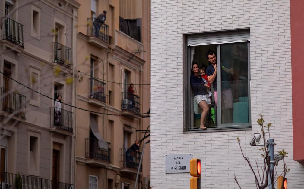 Uma família é vista na janela de sua casa durante um isolamento nacional para combater o novo coronavírus em Barcelona, na Espanha, em 29 de março — Foto: Emilio Morenatti/AP