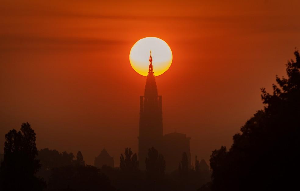 """A catedral de Notre-Dame é vista alinhada ao sol durante o amanhecer em Estrasburgo, na França. O fenômeno, chamado """"Strasbourghenge"""", acontece quando o sol está alinhado diretamente atrás de um edifício ou monumento durante o solstício — Foto: Patrick Hertzog/AFP"""