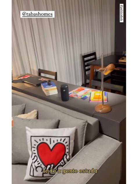 Sala do apartamento tem espaço com sofá e TV, um aparador para trabalho e um espaço com meda de jantar (Foto: Reprodução)