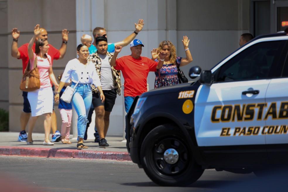 Frequentadores do shopping saem com as mãos ao alto depois de um tiroteio em El Paso, no Texas, neste sábado (3). — Foto: Jorge Salgado/Reuters