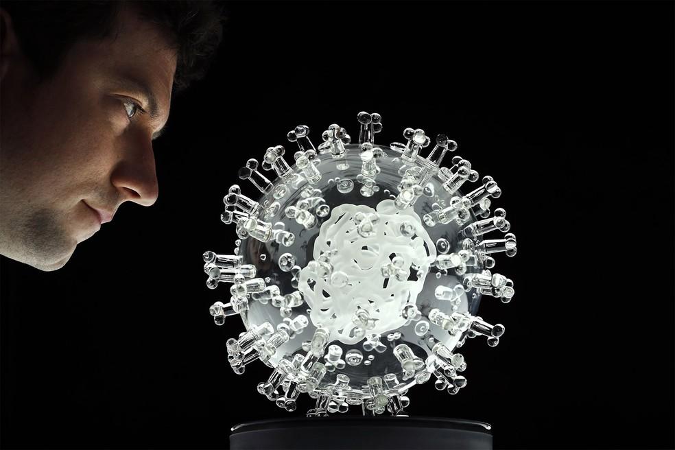 Escultura de vidro representando o coronavírus é apresentada no estúdio do artista britânico Luke Jerram, na Inglaterra. Escultura faz tributo ao esforço médico e científico para combater a pandemia — Foto: Adrian Dennis/AFP