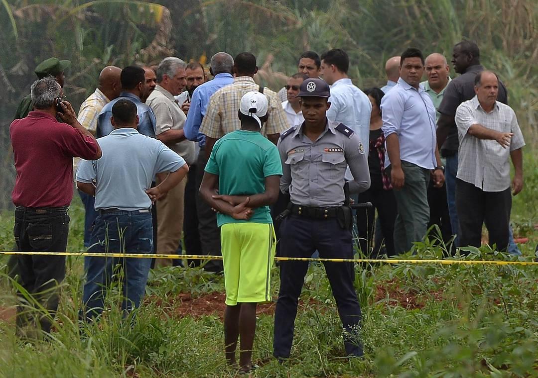 Policial guarda perímetro isolado do público enquanto, ao fundo, o presidente de Cuba, Miguel Diaz-Canel, conversa com um grupo após chegar ao local do acidente aéreo em Havana