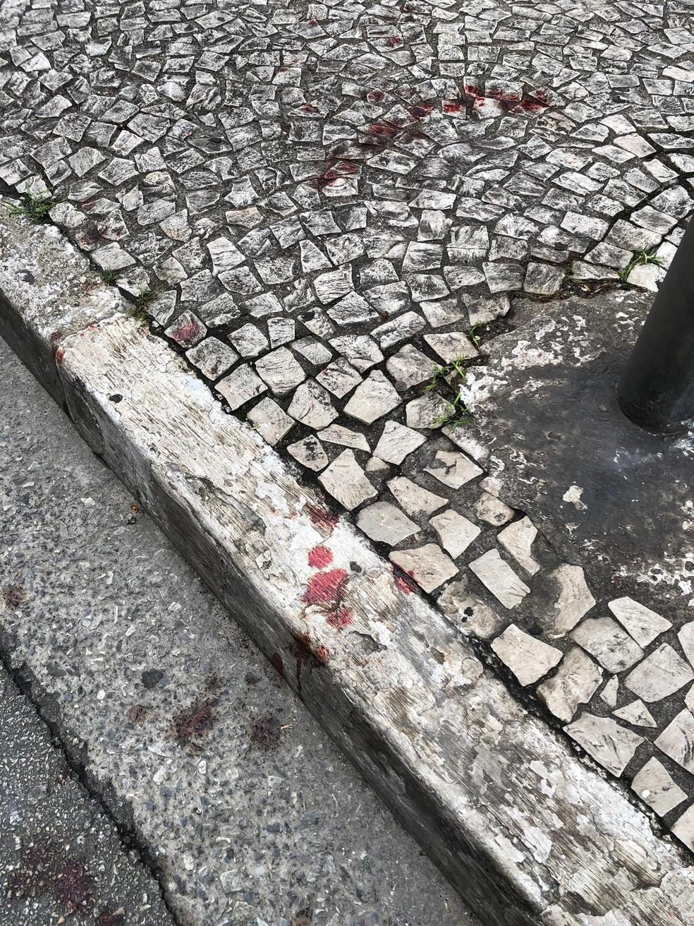 Manchas de sangue na calçada em frente ao bar — Foto: Arquivo pessoal