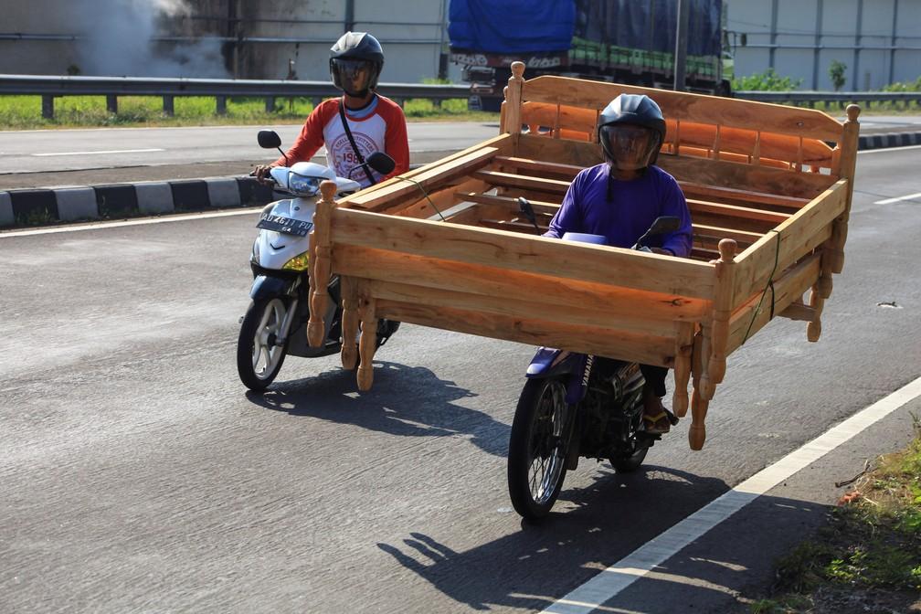 Motociclista é flagrado levando cama de madeira na moto na Indonésia (Foto: Antara Foto/Maulana Surya via REUTERS)