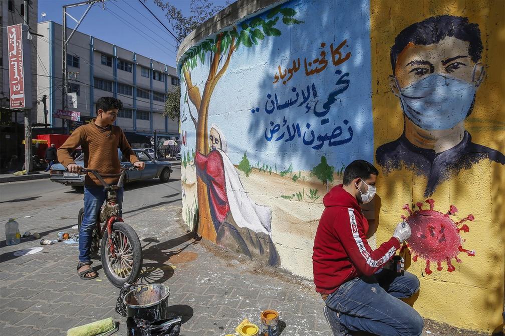 29 de março - Artista palestino finaliza um mural com a frase: 'Combatendo a epidemia, nós protegemos o ser humano e preservamos a Terra', em Rafah, no sul da Faixa de Gaza — Foto: Mohammed Abed/AFP