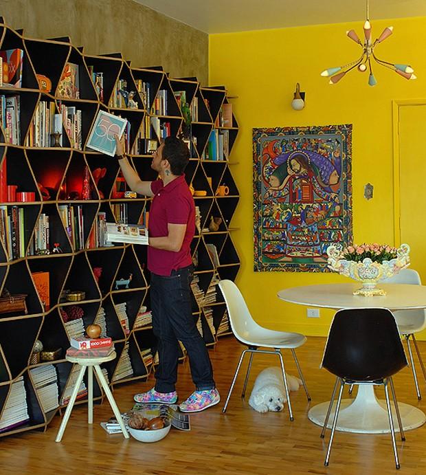 O publicitário Edson Coutinho acomoda seus livros na famosa estante Topo, design de Procter/Rihl. Ele conta com a companhia do podle Tapioca (Foto: Patrícia Cardoso/Casa e Jardim)