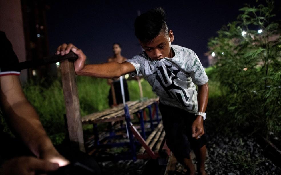 Foto de 19 de outubro mostra menino ajudando a empurrar carrinho de passageiros em linha de trem de Manila — Foto: Noel Celis/AFP