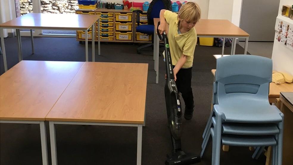 Sammy, de seis anos, disse que estava orgulhoso de poder usar um aspirador de pó, em vez de ter que fazer limpeza à mão — Foto: BBC
