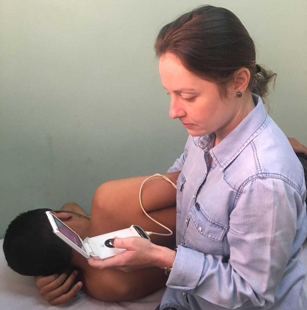 Pesquisadora Lara Castro usa aparelho de ecocardiograma portátil — Foto: HC/Divulgação