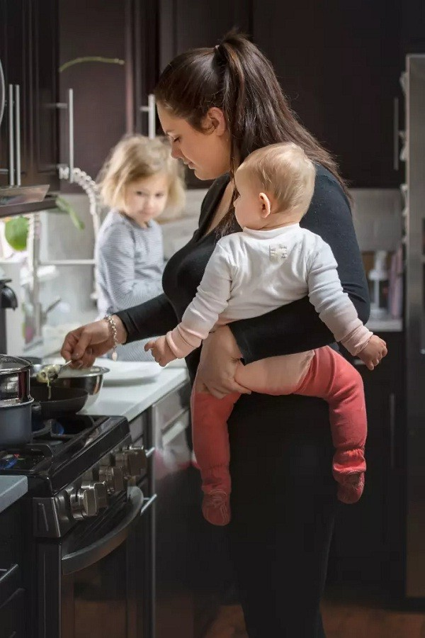 Mãe cozinha com uma única mão enquanto carrega bebê (Foto: Reprodução/Pictures By GG)