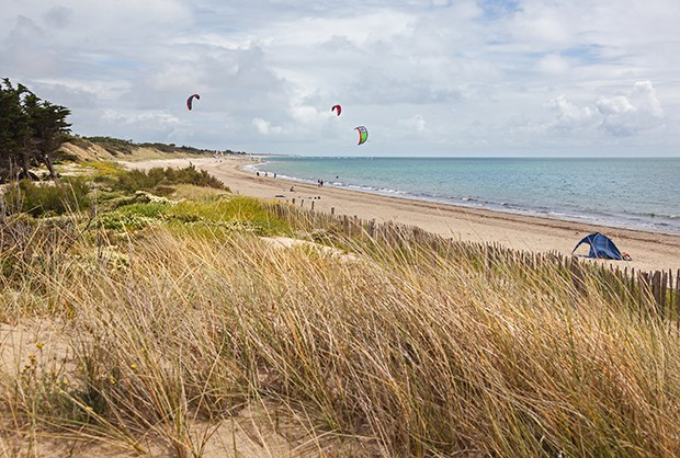 Kite surfing on the deserted Atlantic beach on the island of Ile de Re with dunes covered with grass in the foreground, France (Foto: Getty Images/iStockphoto)