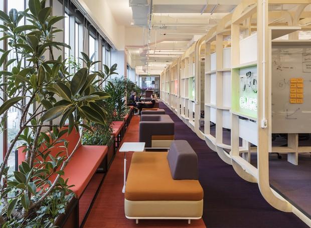 Sofás coloridos correm pelo corredor ao lado dos squads. É uma outra opção de local de trabalho para os funcionários, fugindo das tradicionais mesas de escritórios (Foto: estudio guto requena | 2018)