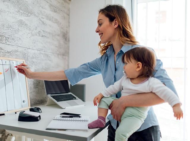 Mulher (mãe) carrega menina (filha) no colo enquanto trabalha em seu escritório (Foto: vgajic/getty images)