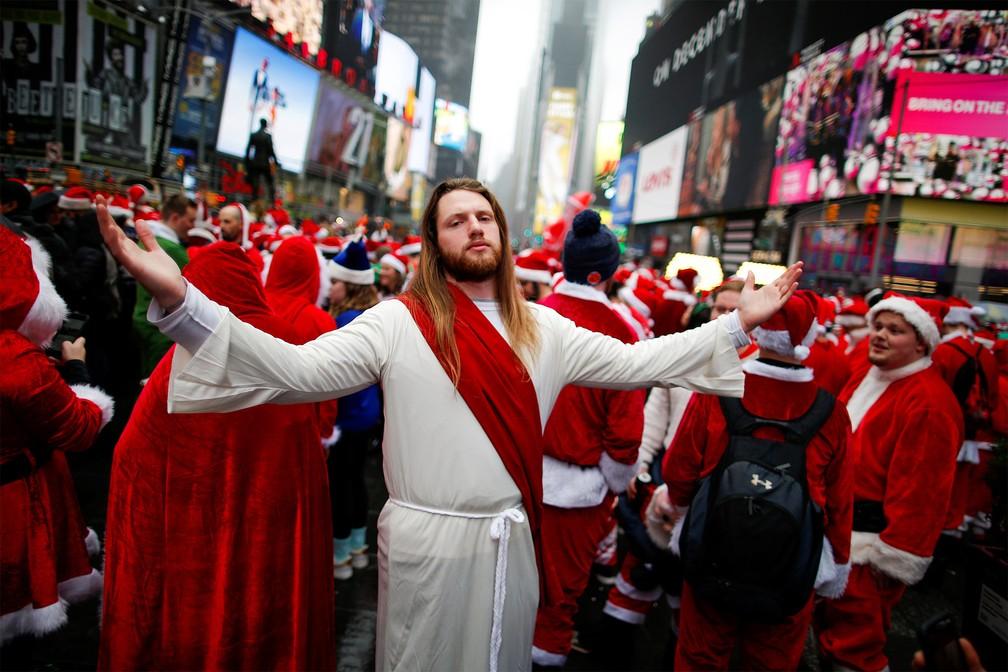 Entre diversos papais noéis, um homem fantasiado de Jesus Cristo faz pose na Times Square, em Nova York, durante evento apelidado de SantaCon, no sábado (14) — Foto: Eduardo Muñoz/Reuters