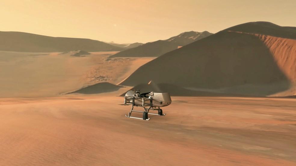 Ilustração mostra robô Dragonfly em aproximação da lua Titã — Foto: Nasa/JHU-APL