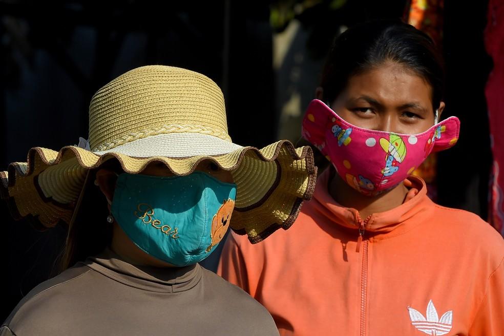 Mulheres usam máscaras de proteção como medida preventiva contra a propagação do novo coronavírus, em um mercado em Phnom Penh, no Camboja — Foto: Tang Chhin Sothy / AFP