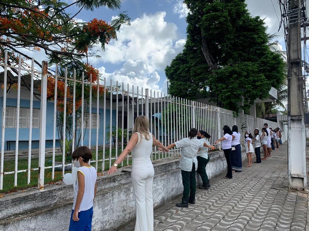 Alunos, pais e funcionários de escola arrombada duas vezes em 24h realizam abraço simbólico em Natal. — Foto: Anna Alyne Cunha/Inter TV Cabugi