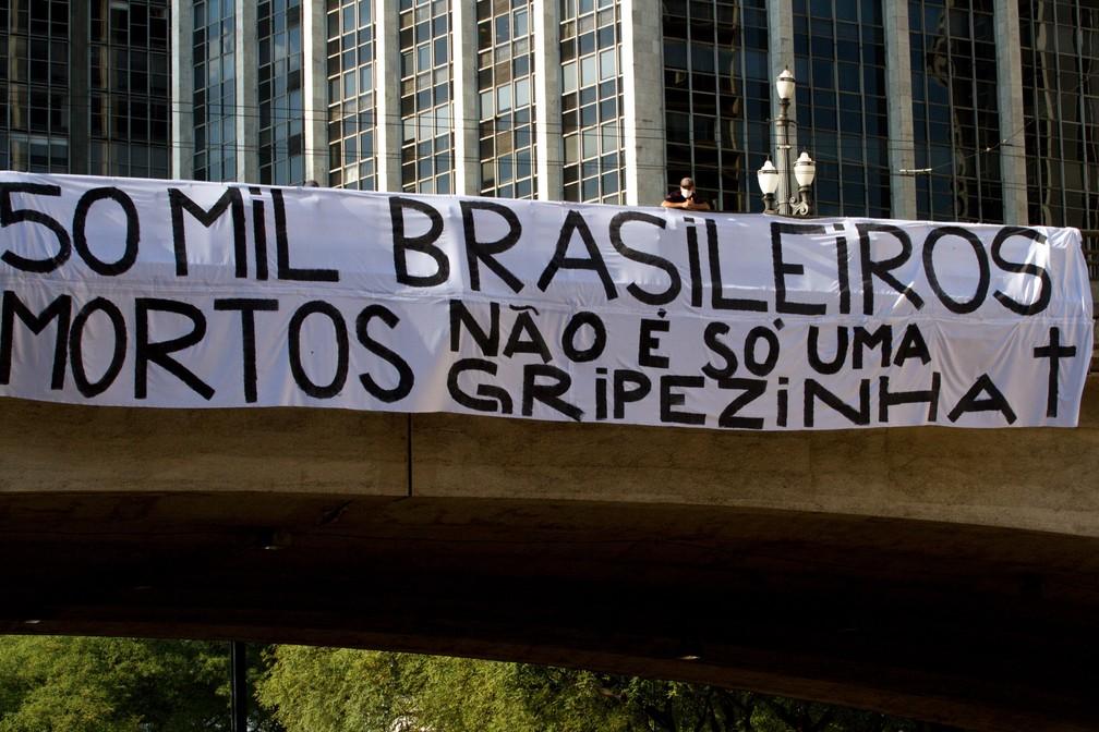 """Faixa com a frase: """"50 mil brasileiros mortos, não é só uma gripezinha"""" é vista pendurada no Viaduto do Chá, no centro de São Paulo (SP), nesta segunda-feira (22). — Foto: BRUNO ESCOLASTICO/PHOTOPRESS/ESTADÃO CONTEÚDO"""