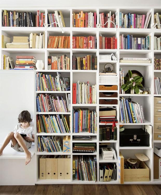 A estante funciona como uma biblioteca e os livros colorem a decoração (Foto: Indecora/ Reprodução)